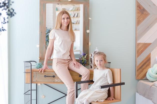 Hermosa madre rubia y linda hijita divirtiéndose y jugando en un piso de moda con un diseño elegante