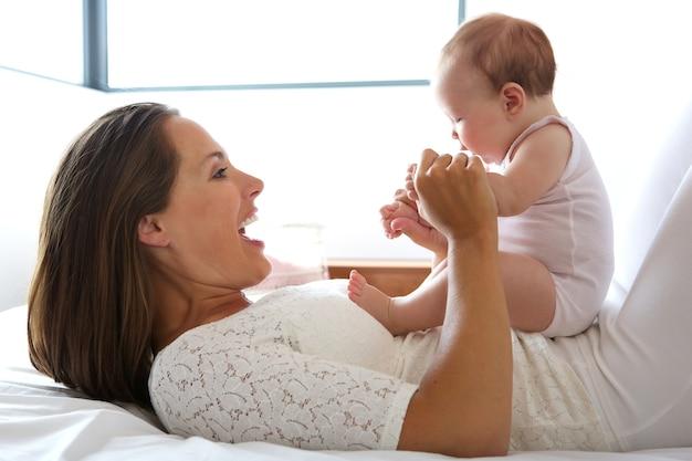 Hermosa madre sonriendo con bebé en la cama