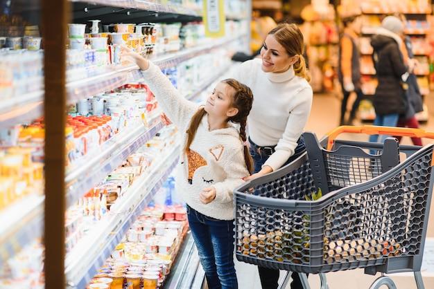 Hermosa madre sosteniendo la cesta de la compra con su hijo caminando en el supermercado