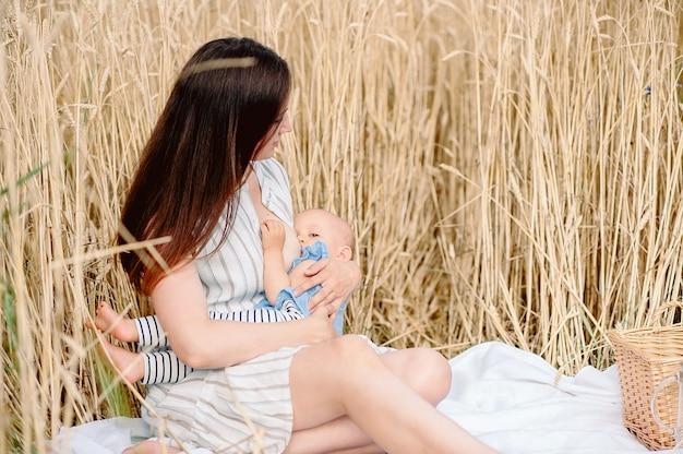 Hermosa madre con su bebé en el campo de trigo