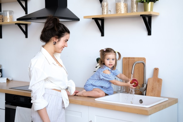 Una hermosa madre con su hija de dos años está lavando frutas en el fregadero de la cocina.