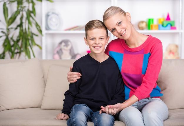 Hermosa madre y su hijo está sentado en el sofá en casa.