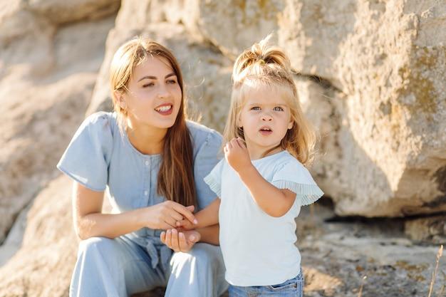 Hermosa madre y su linda hija de pelo largo están caminando sobre una pradera de piedra