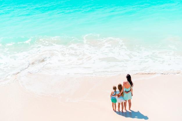 Hermosa madre y su pequeña hija adorable en la playa