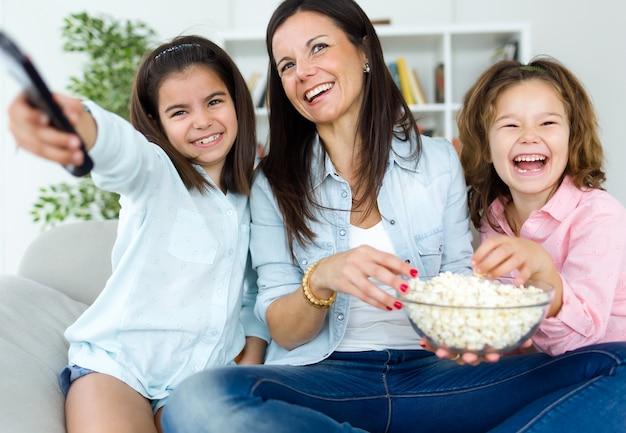 Hermosa madre y sus hijas comiendo palomitas de maíz en casa.