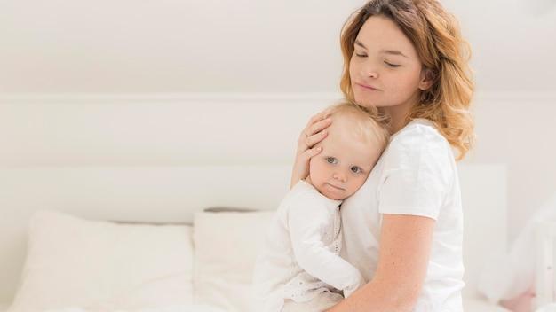 Hermosa mamá abrazando a su bebé
