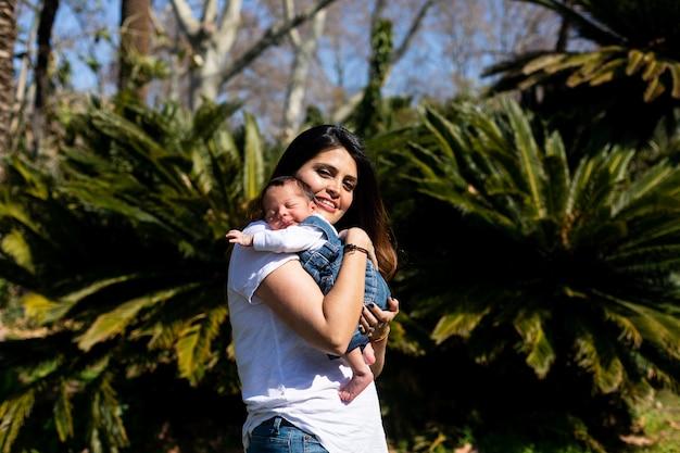 Hermosa mamá con un lindo niño recién nacido durmiendo en la naturaleza al aire libre.