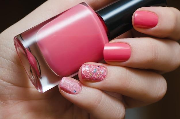 Hermosa mano femenina con cálido diseño de uñas de color rosa.