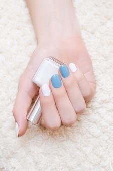 Hermosa mano femenina con diseño de uñas azul y blanco
