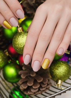 Hermosa mano femenina con diseño de uñas de color beige. manicura de navidad.