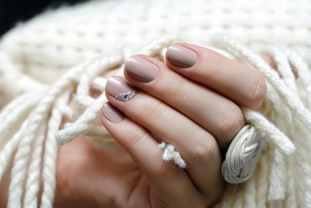Hermosa mano femenina con diseño de uñas de color beige.