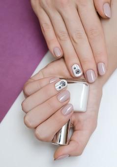 Hermosa mano femenina con diseño de uñas de diente de león.