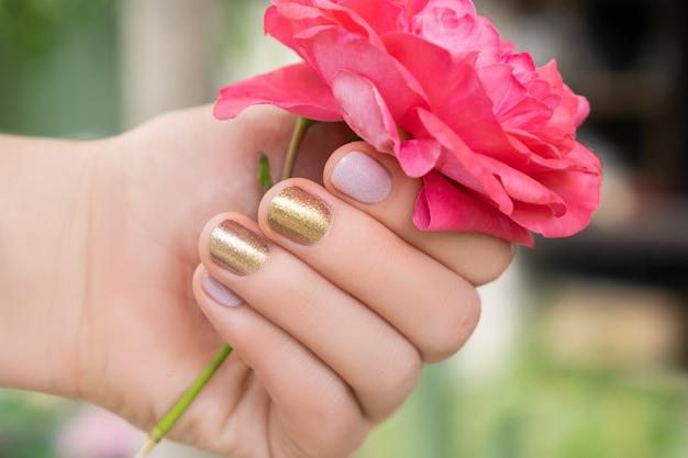 Hermosa mano femenina con un diseño perfecto de uñas doradas y rosadas que sostiene una flor rosa fresca