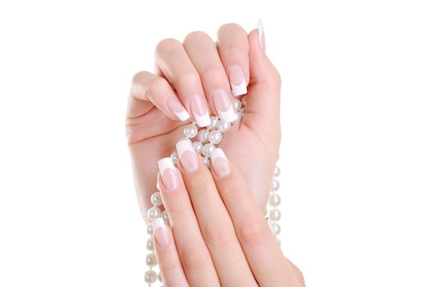 Hermosa mano femenina elegante con manicura francesa de belleza sobre