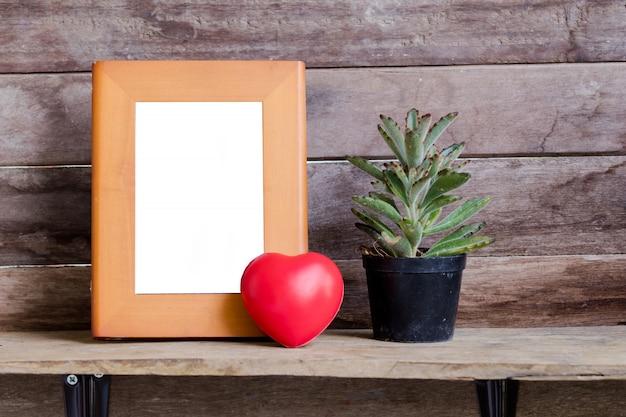 Hermosa maqueta de marco de madera decorada con corazón de san valentín y cactus