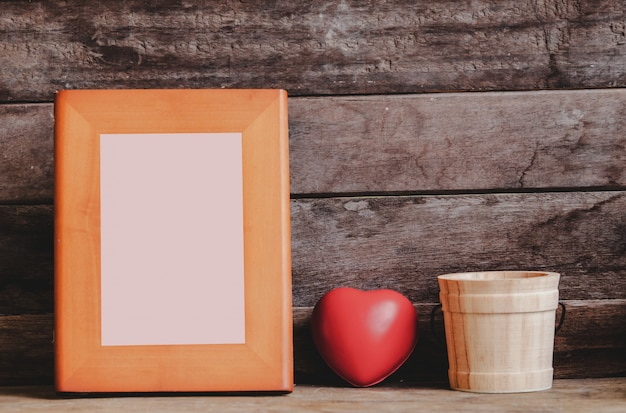 Hermosa maqueta de marco de madera en el estante decorado con corazón de san valentín y cactus