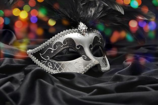 Hermosa máscara de carnaval veneciano sobre tela oscura y luz colorida