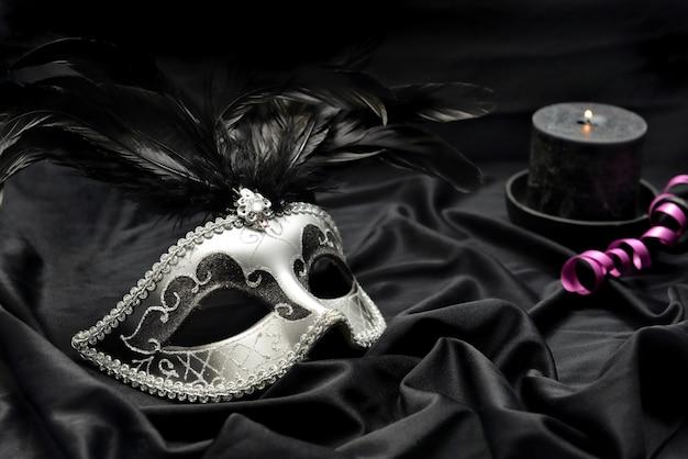 Hermosa máscara de carnaval veneciano sobre tela oscura con vela y cinta