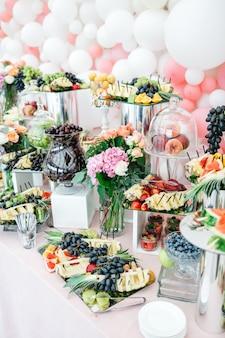 Hermosa mesa con dulces y frutas para invitados.