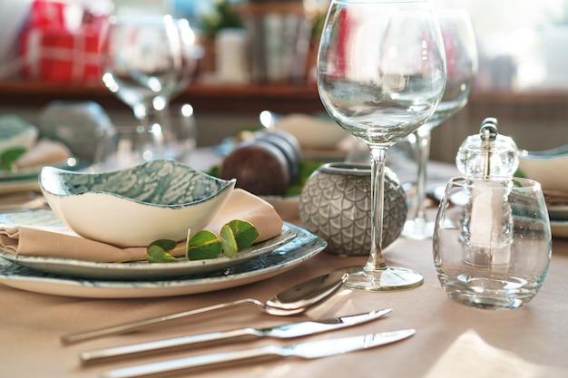 Hermosa mesa elegante con vajilla verde elegante y cubiertos de plata.