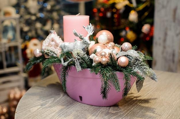 Hermosa mesa de navidad composición decorativa con velas, ciervos de juguete, bolas de cristal y abeto en florero rosa