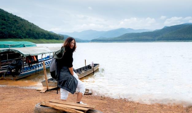 Una hermosa mochila de mujer turista esperando un taxi en el río con el agua de la montaña y el cielo como telón de fondo.