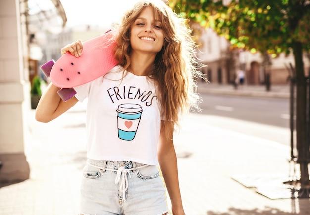 Hermosa modelo de adolescente rubia linda sin maquillaje en ropa blanca hipster de verano con patín rosa centavo posando en el fondo de la calle