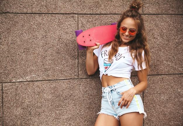 Hermosa modelo de adolescente rubia linda sin maquillaje en ropa blanca hipster de verano con patineta rosa centavo posando junto a la pared en la calle