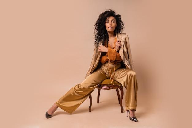 Hermosa modelo africana con perfectos pelos rizados en elegante blusa naranja y pantalones de seda sentada en la pared beige de la silla vintage.
