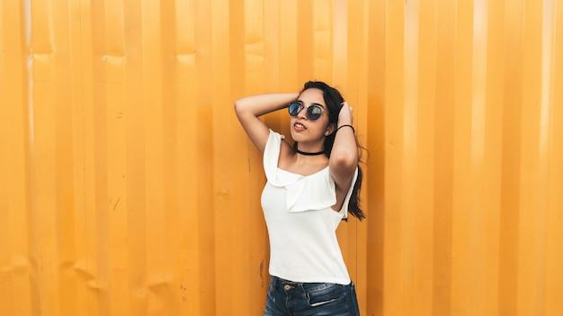 Hermosa modelo brasileña posando contra la pared naranja