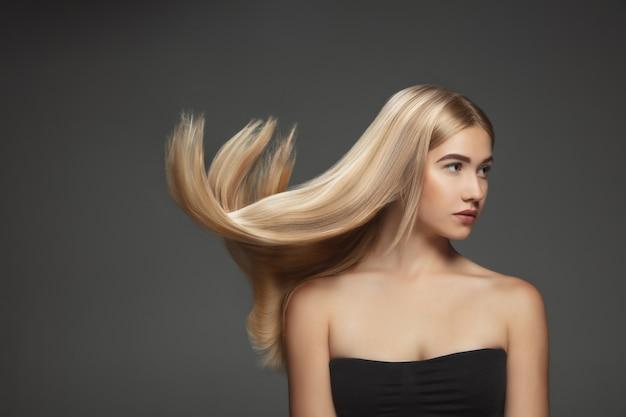 Hermosa modelo con cabello rubio largo, liso y volador aislado sobre fondo gris oscuro de estudio. modelo caucásico joven con piel bien cuidada y cabello soplando en el aire.