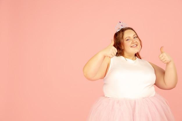 Hermosa modelo caucásica regordeta de talla grande en traje de hada aislado sobre fondo rosa.