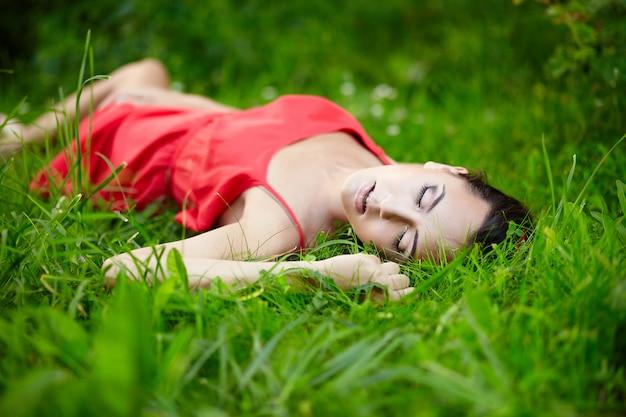 Hermosa modelo de chica morena femenina tumbada en verano verde hierba brillante en el parque con maquillaje en vestido rojo