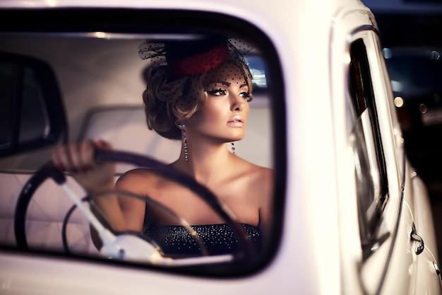 Hermosa modelo de chica rubia de moda sexy con maquillaje brillante y peinado rizado en estilo retro sentado en un auto viejo