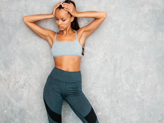 Hermosa modelo con cuerpo bronceado perfecto. mujer posando en estudio cerca de la pared gris