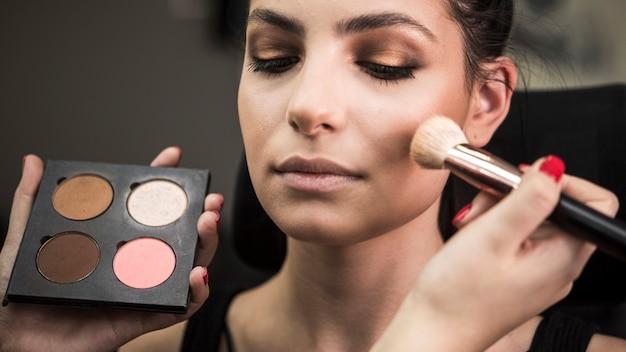 Hermosa modelo en estudio de maquillaje