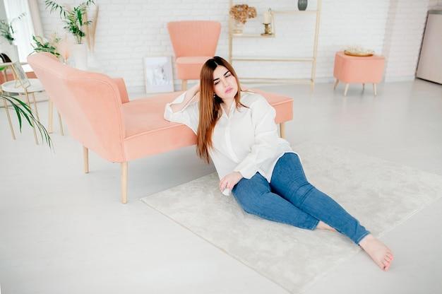 Hermosa modelo femenina de talla grande vestida con camisa blanca en blanco posando sobre el fondo de una habitación luminosa