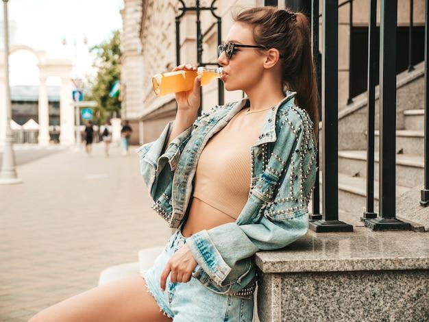 Hermosa modelo linda sonriente en ropa de chaqueta de jeans hipster de verano posando en la calle