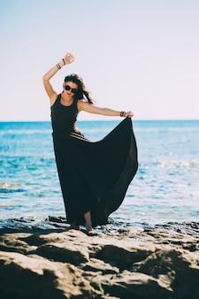 Hermosa modelo de moda en la playa con hermoso vestido largo.
