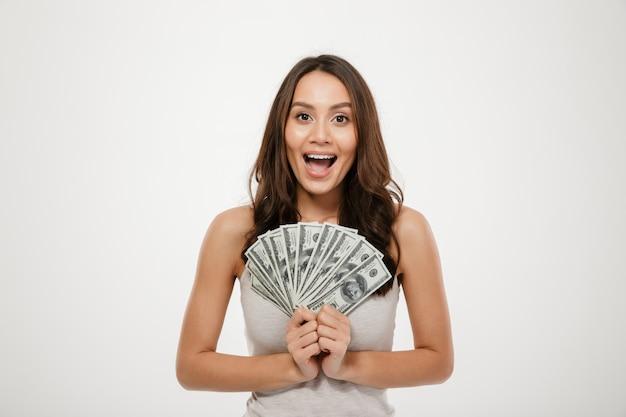 Hermosa modelo morena con cabello largo con abanico de billetes de 100 dólares, ser rica y feliz sobre la pared blanca