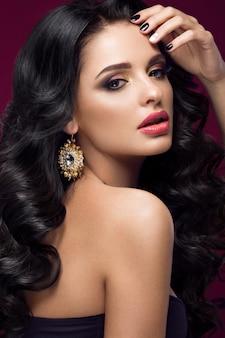Hermosa modelo morena: rizos, maquillaje clásico, joyas de oro y labios rojos. la cara bonita.