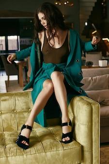 Hermosa modelo morena sensual en traje de moda relajante en el sofá