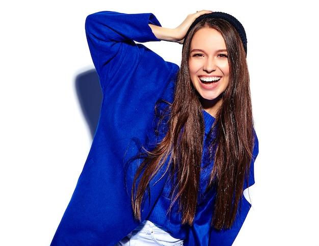 Hermosa modelo de mujer morena hipster sonriente en elegante abrigo azul aislado en blanco