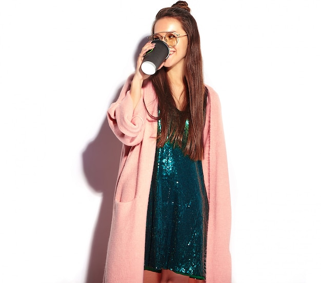 Hermosa modelo de mujer morena hipster sonriente en elegante abrigo rosa. bebiendo café