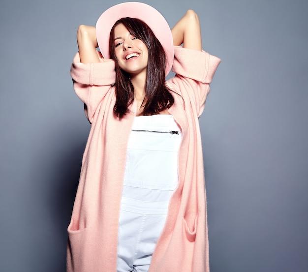 Hermosa modelo de mujer morena hipster sonriente en elegante abrigo rosa y colorido sombrero posando en gris