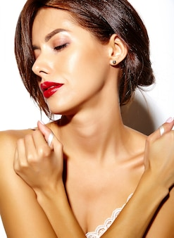 Hermosa modelo de mujer sexy caliente bronceada con hombros desnudos y labios rojos sobre fondo blanco