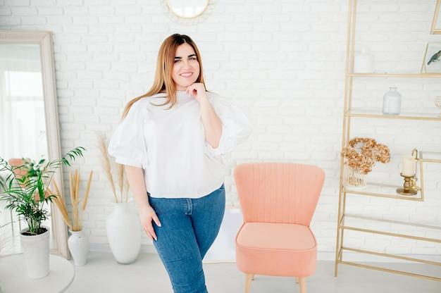 Hermosa modelo mujer de talla grande con camisa blanca posando en el fondo de una acogedora habitación