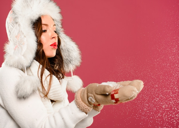 Hermosa modelo de navidad soplando copos de nieve