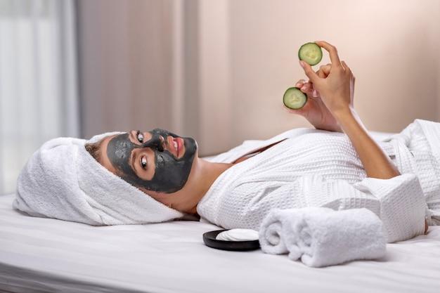 Hermosa modelo posa con una máscara de arcilla en la cara