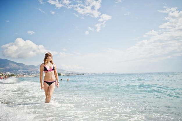 Hermosa modelo relajante en una playa vestida con un traje de baño.